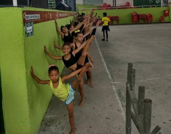 Meninas fazem exercício apoiadas na parede.